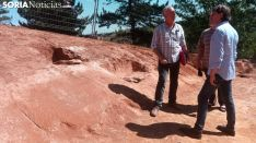 El alcalde (dcha.) frente al director de las obras, junto a las sepulturas encontradas. /SN