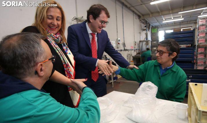 Fernández Mañueco, junto con Yolanda de Gregorio, saluda a una empleada en el centro de Asovica. /SN
